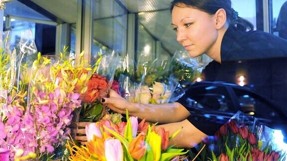 Frau arrangiert Blumensträuße im Moskauer NAT-Floristikstudio.