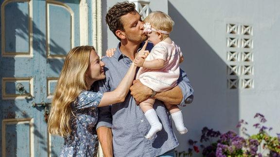 Ein Familienvater hält sein kleines Kind auf dem Arm und küsst es auf die Stirn. Neben ihm steht seine Frau, die dem kleinen Mädchen mit dem Finger auf die Nase stupst. Das Kind schaut sie an und lacht.