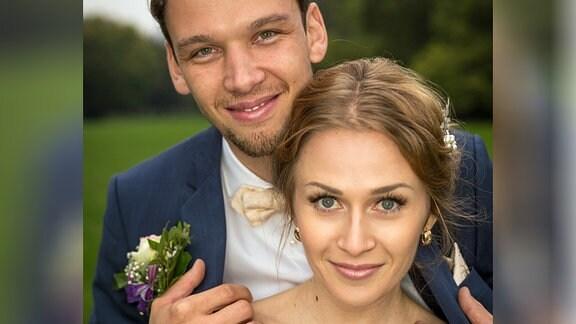 Ein Brautpaar lächelt in die Kamera. Er trägt ein dunkelblaues Sakko und wsein weißes Hemd und hält sie in seinen Armen, an seiner rechten Hand gut sichtbar der Ring. Sie trägt ein weißes Brautkleid und hält einen Blumenstrauß in der Hand.
