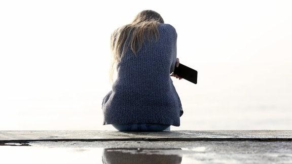 Eine Frau mit Smartphone in der Hand sitzt auf einer Freitreppe und wirkt besorgt.