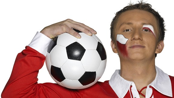 Ein junger Mann in rot-weißem Trikot und mit einem Fußball