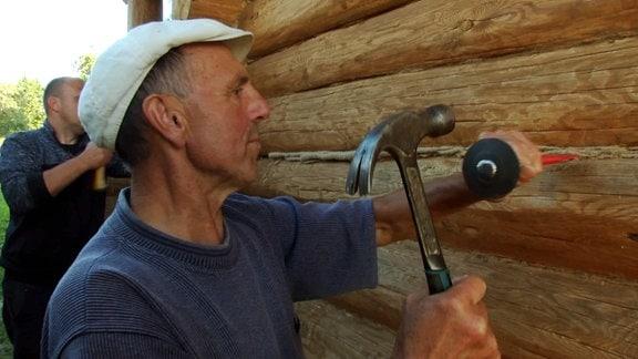 Mann mIt Hammer arbeitet an einer Holzwand.