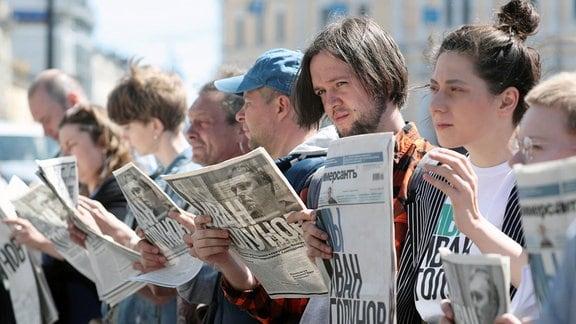 Menschen halten Zeitungen in den Händen.