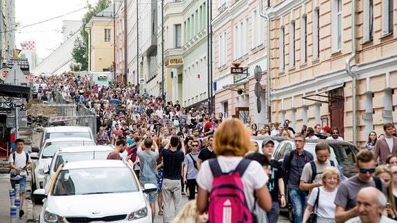 Große Menschenmenge marschiert durch eine Straße.