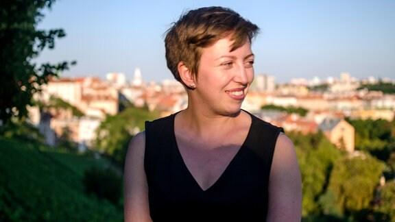 Eine junge Frau mit kurzen, braunen Haaren in einem schwarzen Kleid schaut nach rechts aus dem Bild. Im Hintergrund ist unscharf das Panorama einer sonnenbeschienen Stadt zu erkennen