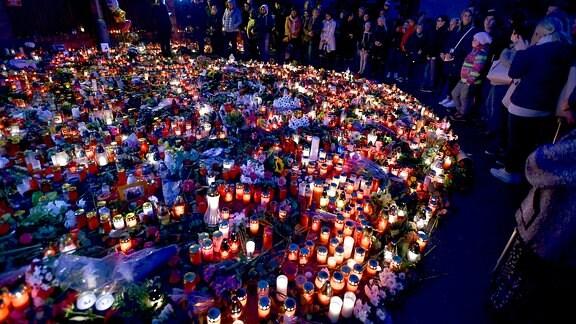 Viele Menschen stehen mit angezündeten Kerzen vor dem Haus von Karel Gott in Prag.