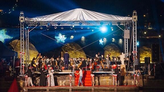 Ein Orchester spielt am Abend, an einem Fluss, auf einer Bühne.