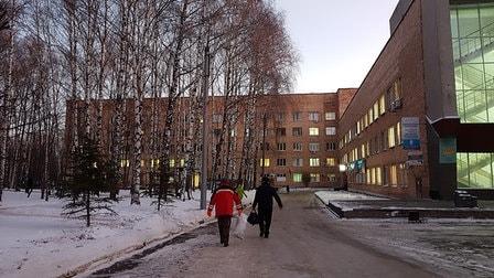 Drei Personen in Anoraks laufen auf einem teilweise vereisten Fußweg. Links ist eine schneebedeckte Fläche zu sehen, auf der viele Birken stehen. Im Hintergrund ist ein roter unscheinbarer Neubau. Bildunterschrift: Das Semaschko-Krankenhaus in Nischni Nowgorod.