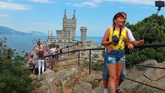 Urlauber vor Burg auf Felsen an Meeresbucht