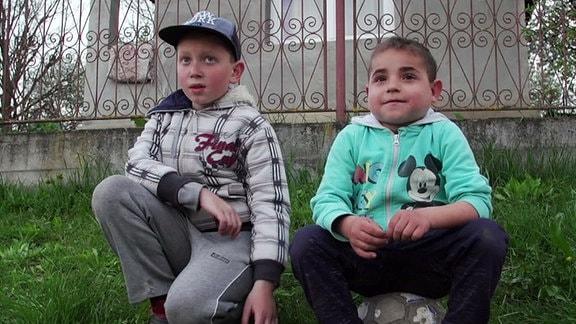 zwei kleine Jungen hocken vor einem Haus
