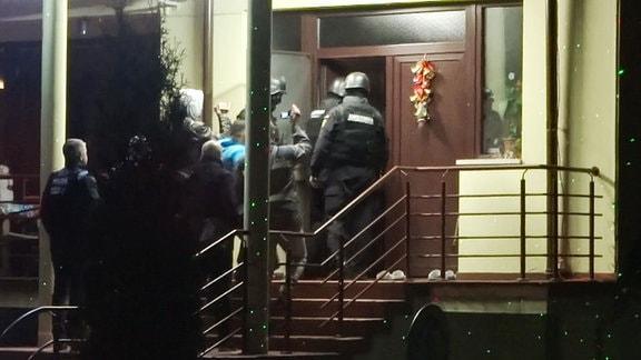 Männer einer Spezialeinheit gehen Treppe zu einem Haus hoch