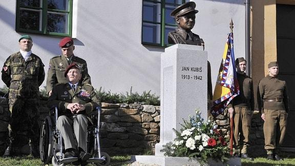 Soldaten am Denkmal des Widerstandskämper Jan Kubiš, ein Veteran im Rollstuhl.
