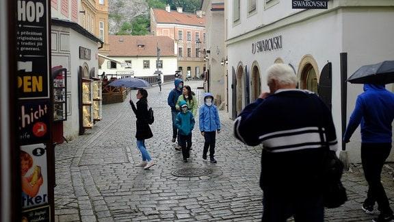 Menschen laufen im Regen durch eine Stadt