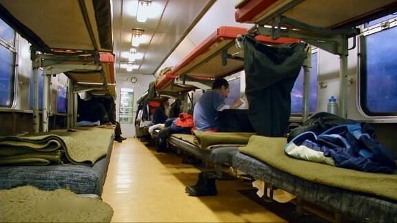 Zugwagon von innen mit mehreren belegten Betten