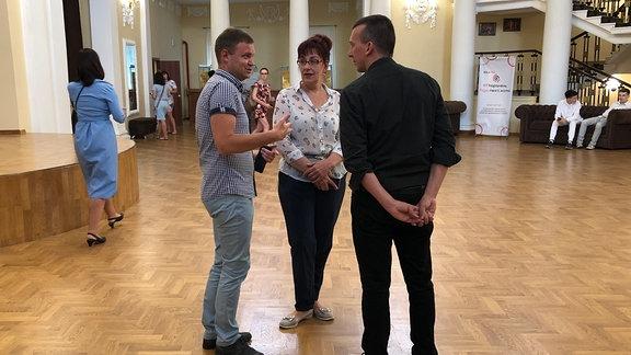 Theaterdirektor Sergej Dorofeev unterhält sich mit Projektorganisator Peter Schwarz und einer Mitarbeiterin.