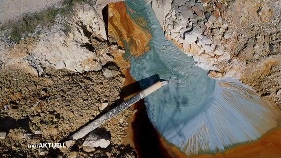 Abwasser aus Kupferbergbau läuft aus einem Rohr in einen See