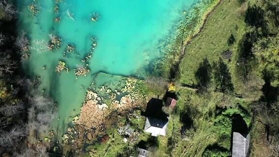Ein Dorf versunken in Wasser, das azurblau durch Chemikalien glänzt.