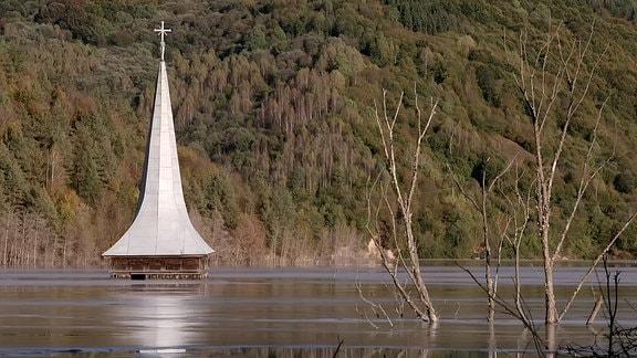 Ein Kirchturm ragt aus dem Wasser heraus.
