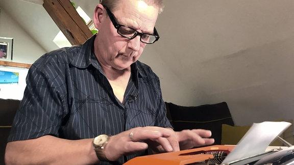 Ein Mann sitzt vor einer Schreibmaschine und tippt auf dieser.