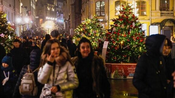 Menschen gehen an geschmückten Weihnachtsbäumen vorbei