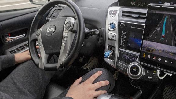 In einem Atonomen Fahrzeug fährt ein Testfahrer