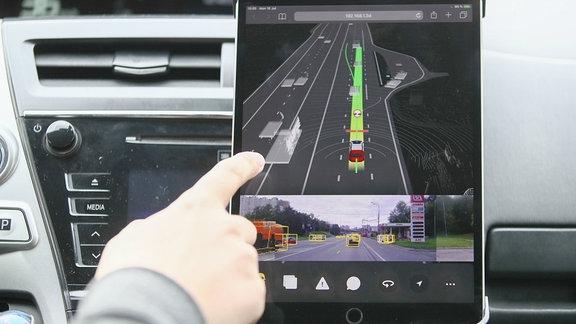 Finger eines Autofahrers weist auf ein Display