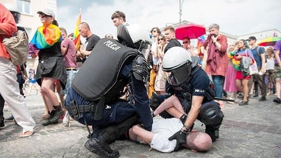 Polizisten halten einen Mann gewaltsam am Boden. Hinter ihnen laufen demonstrierende Menschen.