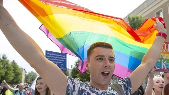 Ein junger Mann schwenkt fröhlich die Regenbogenfahne über seinem Kopf.