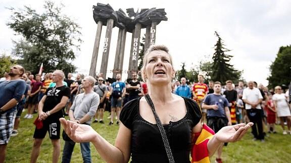 Eine Frau ateht mit anderen Menschen auf einer Wiese und demonstriert.