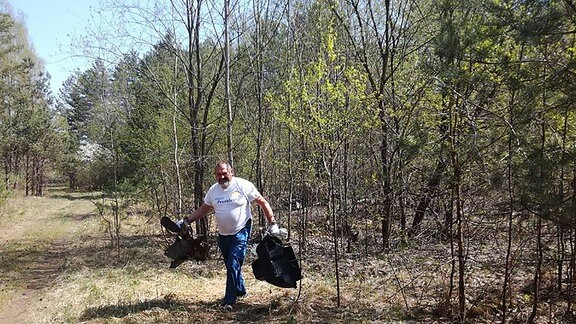 Ein Mann trägt größere Teile aus dem Wald.