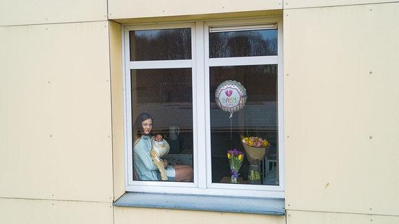 Eine Frau mit Baby im Arm sitzt am Fenster
