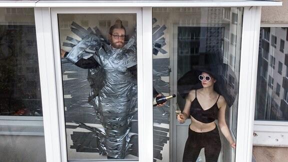 Ein Mann mit Glebestreifen fixiert am Fenster und eine Frau im Kostüm