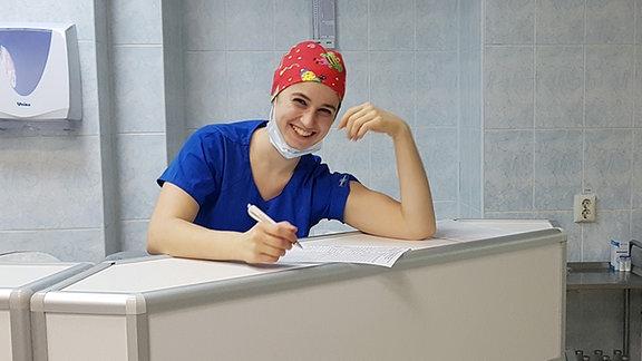 Eine junge Frau in blauem Krankenschwester-Kittel mit roter Haube steht hinter einem Tresen und hält einen Stift in der Hand. Sie lächelt in die Kamera. Hinter ihr stehen Regale mit Krankenhausutensilien. Bildunterschrift: Maria Görlitz während Ihres Freiwilligendienstes in Nischni Nowgorod.