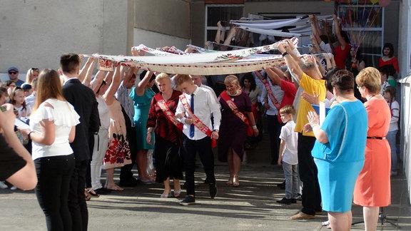 Jugendliche laufen unter von Erwachsenen aufgespannten Bannern entlang.