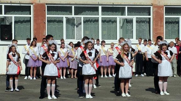 Mädchen in festlicher Kleidung tanzen synchron auf einem Schulhof.