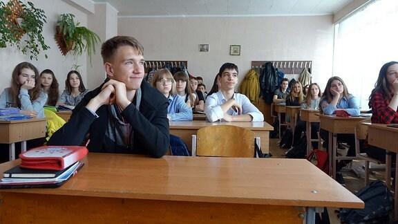 Schulklasse hört im Klassenraum Lehrerin zu.
