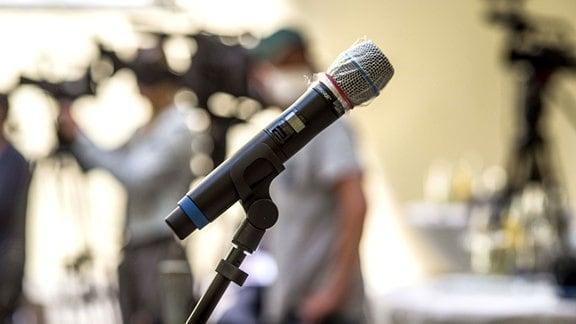 Ein Mikrofon mit Plastikschutz vor Coronaviren auf einer Pressekonferenz.