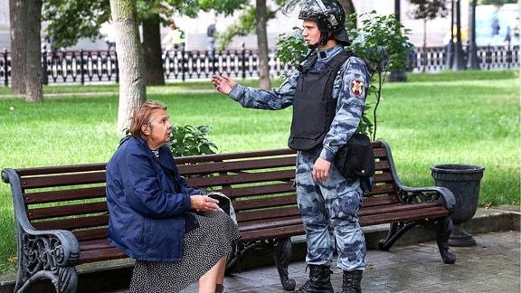 Eine Frau und ein Bereitschaftspolizist sprechen während einer Kundgebung in Moskau