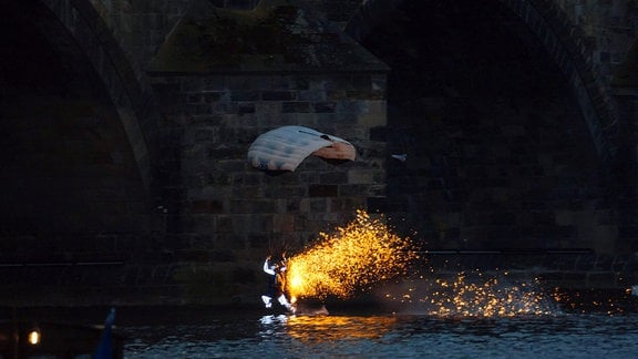 Fallschirmspringer sprüht Funken über Fluss