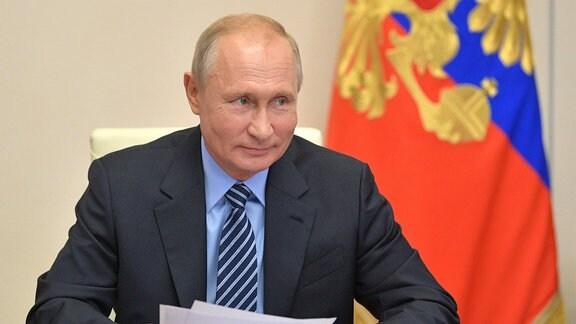 Präsident Putin sitz an einem Tisch während einer Videokonferenz.