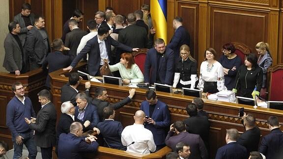 Parlamentarier blockieren eine Tribüne während einer Sitzung des ukrainischen Parlaments