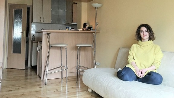 Eine Frau sitzt auf einem Sofa.