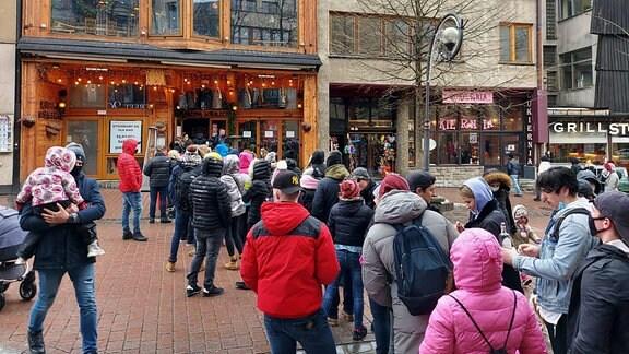 Menschen stehen vor einem Restaurant
