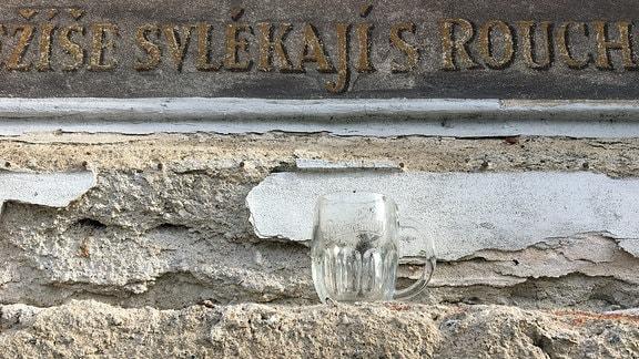Ein abgestellter Pilsner-Urquell Bierkrug an der Kreuzwegstation.