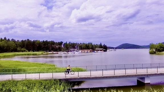 Frau fährt mit Fahrrad über brücke von Macha-See