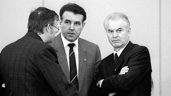 V.r.n.l.: Ministerpräsident Hans Modrow (DDR) im Gespräch mit Innenminister Lothar Ahrendt (DDR) und Peter Moreth (DDR/Minister für örtliche Organe) während einer Sitzung des Runden Tisches in Ost-Berlin, 1990.