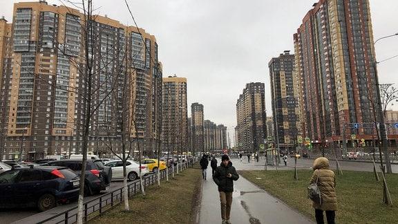 Fußgänger auf einer Straße zwischen gelben Hochhäusern bei grauem Himmel.