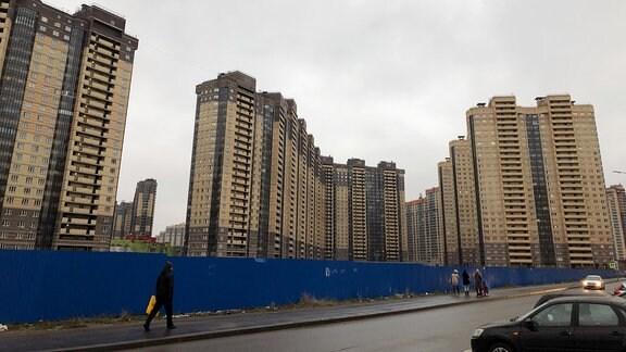 Fußgänger vor Baustellenabsperrung. Im Hintergrund gelbe Hochhäuser bei grauem Himmel.