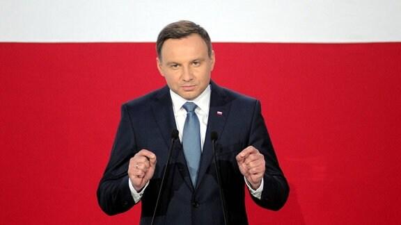 Polens Präsident, Andrzej Duda, steht vor der polnischen weiß-roten Flagge.