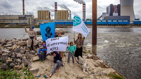 Auf einem kleinen Strandabschnitt gegenüber einem Kraftwerk haben Künstlerinnen Transparente ausgerollt.